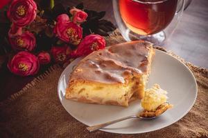 un pezzo di torta di mele su un piatto bianco su uno sfondo di fiori rosa foto