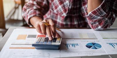 primo piano contabile o esperto finanziario analizzare il grafico del rapporto di affari e il grafico delle finanze presso l'ufficio aziendale. concetto di economia finanziaria, attività bancarie e ricerche di mercato azionario foto