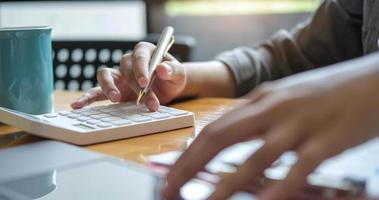 Chiudere le mani di imprenditrice o ragioniere tenendo la penna e lavorando sulla calcolatrice per calcolare i dati aziendali, documenti contabili e computer portatile in ufficio, concetto di business foto