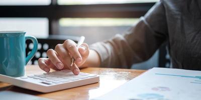 una donna d'affari utilizza un laptop per calcolare i risultati degli investimenti. e fare rapporti finanziari sul concetto di contabilità di finanza aziendale scrivania foto