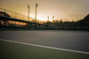 messa a fuoco selettiva della linea di base di un campo da tennis con uno sfondo di cielo al tramonto. paesaggio del luogo sportivo. foto