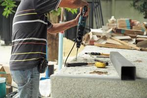 messa a fuoco selettiva sulle mani del lavoratore tenere il trapano durante la perforazione sul pavimento di cemento. foto