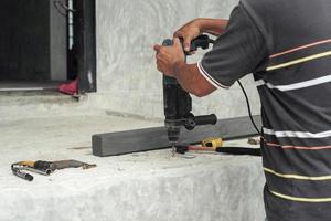 messa a fuoco selettiva sulle mani del lavoratore tenere il trapano durante la perforazione sul pavimento di cemento in cantiere foto