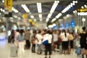 gruppo sfocato di passeggeri che effettuano il check-in allo sportello per una carta d'imbarco in aeroporto. immagine sfocata apposta foto