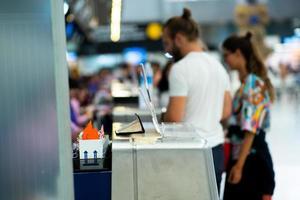 messa a fuoco selettiva sul bancone metallico della compagnia aerea in aeroporto con passeggeri sfocati che effettuano il check-in in background. foto