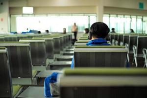indietro ritratto di un uomo che ascolta la musica con un auricolare in attesa del volo nella sala del terminal delle partenze foto