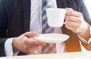 da vicino, giovane uomo d'affari in possesso di una tazza di caffè bianco in ufficio foto