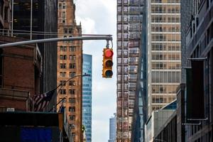 semaforo con luce rossa sopra manhatan street tra molti grattacieli foto