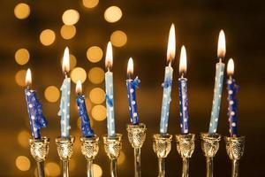 piccole candele e menorah vicino a luci astratte foto
