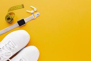 scarpe da ginnastica e un orologio sportivo con copia spazio su sfondo giallo foto