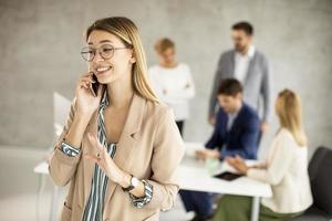 donna d'affari sul telefono con riunione in background foto