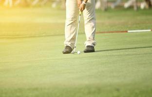 uomo che mette sul campo da golf foto