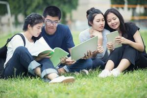 studenti asiatici che studiano sul prato foto