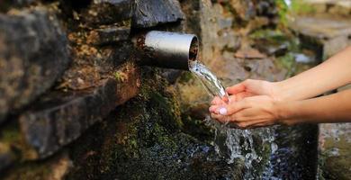 striscione di donna che raccoglie acqua pura in mano dalla sorgente nel muro foto