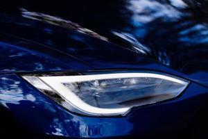 primo piano del nuovo faro del proiettore sulla moderna automobile blu foto