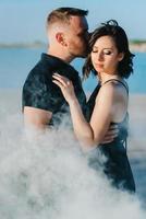 ragazzo e una ragazza in abiti neri si abbracciano all'interno del fumo bianco foto