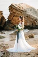 sposa con un bouquet da sposa sulla riva foto