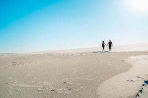 giovane coppia un ragazzo e una ragazza con emozioni gioiose in abiti neri camminano attraverso il deserto bianco foto