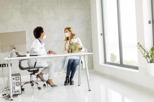 bambino e genitore che prendono con il medico foto
