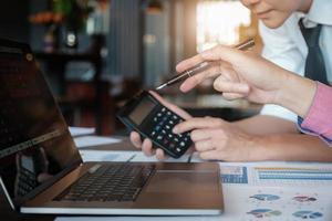 discussioni di ricerca economica, squadra di affari che analizza tabelle di reddito e grafici per pianificare il concetto di marketing con l'utilizzo di computer portatile e penna per l'analisi. foto
