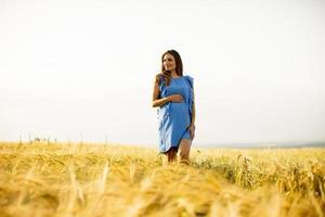 donna incinta che cammina in un campo di grano foto