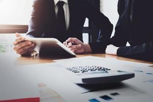 squadra di affari che analizza i grafici e le tabelle di reddito per pianificare il concetto di marketing con l'utilizzo di tablet e calcolatrice per l'analisi foto