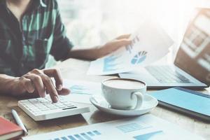 il ragioniere sta premendo la calcolatrice per il calcolo controlla l'accuratezza del budget di investimento utilizzando il laptop del computer e documenta i dati per l'analisi foto