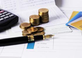 Close up della penna stilografica con pila di monete e carta di credito foto