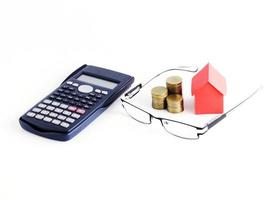 calcolatrice e occhiali da vista con pila di monete e carta di casa su sfondo bianco foto