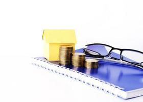 pila di monete e casa di carta e occhiali da vista sul libro blu per il concetto di business su sfondo bianco foto
