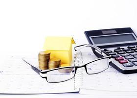 occhiali e monete pila e casa di carta e calcolatrice sulle pagine del libro del calendario per il concetto di business foto