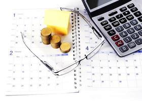 concetto di affari con occhiali e monete pila e casa di carta e calcolatrice sulle pagine del libro del calendario foto