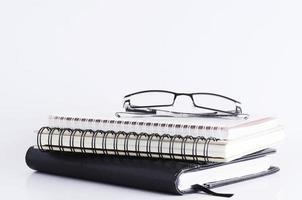 occhiali da vista sulla pila di libri per il concetto di business foto