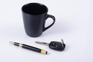 tazza di caffè con chiave auto e penna stilografica affari su sfondo bianco foto