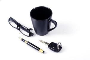 tazza di caffè con occhiali, chiave della macchina e penna per un concetto di stile minimalista con spazio per il testo foto
