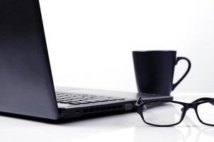 Close up di occhiali con computer portatile e tazza di caffè su sfondo bianco per il concetto di tecnologia lifestyle foto