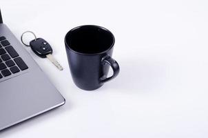 concetto di tecnologia di vita con tazza di caffè, chiavi della macchina e computer portatile su sfondo bianco foto