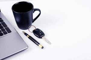 tazza di caffè e penna stilografica e chiave della macchina con il computer portatile su sfondo bianco con copia spazio per il testo foto