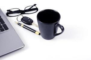 tazza di caffè con chiave della macchina e penna stilografica e occhiali da vista su sfondo bianco foto