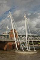 Vista dei ponti del giubileo d'oro e la stazione di Charing Cross dalla riva sud del fiume Tamigi a Londra in una torbida giornata estiva foto
