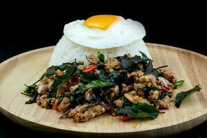 Maiale fritto piccante con riso ricoperto di foglie di basilico, uova fritte su un piatto di legno, pad krapow moo è il cibo tailandese tradizionale foto