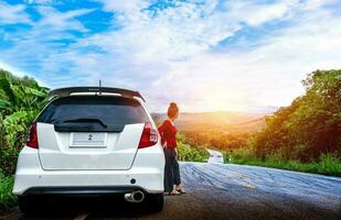 giovane bella signora in piedi vicino a un'auto rotta che chiede aiuto sulla strada pubblica in una zona boschiva foto
