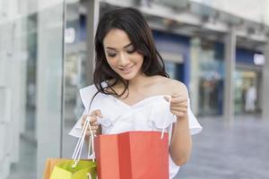 donna che guarda in borsa della spesa foto