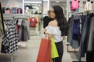 signora asiatica che tiene borse e shopping nel centro commerciale foto