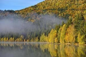 paesaggio autunnale in montagna con alberi che riflettono nell'acqua a st ana lago romania foto