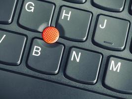 una foto del primo piano del bastone di puntamento rosso sulla tastiera di un laptop