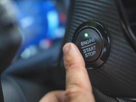 il dito del conducente sta premendo il pulsante di avviamento dell'auto foto