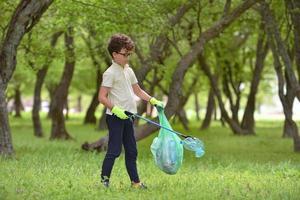 giovane ragazzo raccoglie spazzatura in una foresta di primavera al tramonto foto