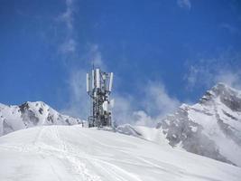 antenna e ricetrasmettitore 5g, 4g in cima alle montagne in inverno con la neve foto