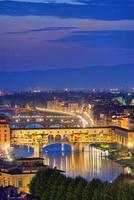 vista notturna del fiume arno e del famoso ponte vecchio foto